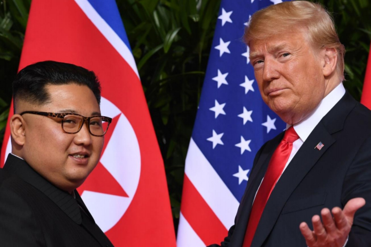 Kim Jong-un and Donald Trump face each other with their nations' flags in background.