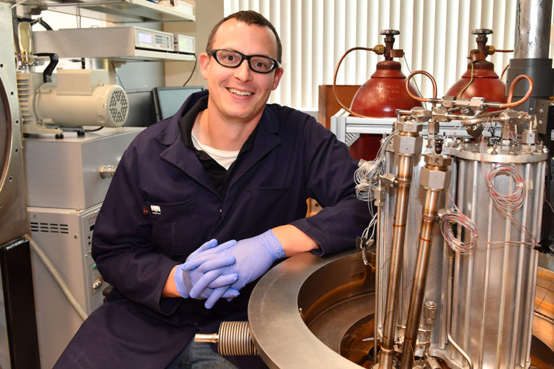 Leachman in lab with tanks of gas beside him.