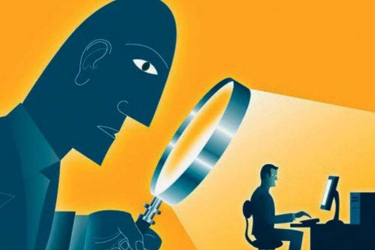 Cartoon of looming figure looking through magnifying glass at man at computer.