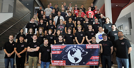 Members of the Cougs in Space club pose on a stairway holding a club banner.