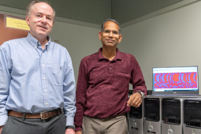 Belzer and Sivakumar stand beside a row of computer servers.