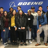 Students gathered in front of wall with Boeing logo.