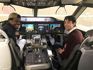 Students sitting in pilot and co-pilot seats in replicated cockpit at Boeing.