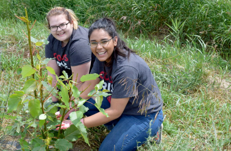 Two female students tend to a plant in a garden.