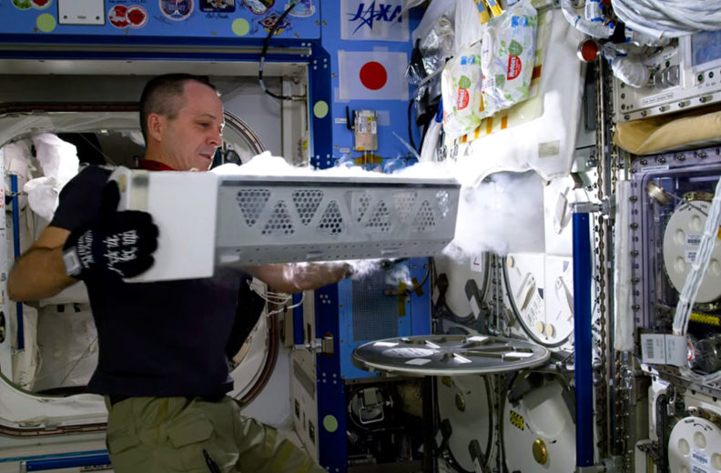 Arnold pulls tray out of cold storage aboard ISS.
