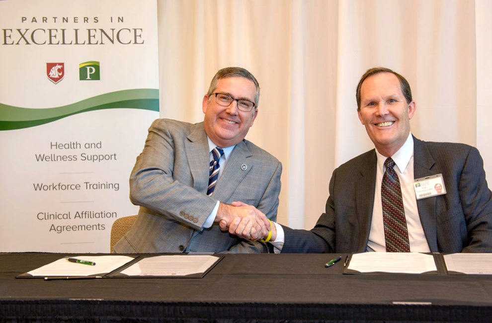 Schulz and Adams shake hands during formal signing.