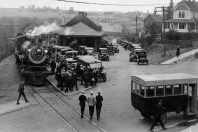 Historic photo of Pullman train depot featuring train, cars and people.