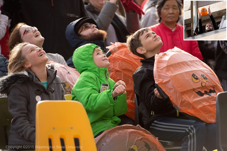 Parents and children look up as a pumpkin is dropped from Webster Hall.
