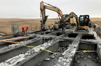 Excavators remove debris during bridge construction.