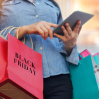 Woman using tablet and holding Black Friday shopping bags.