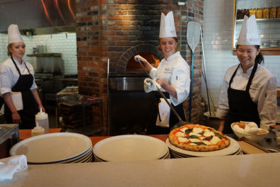 Jacobs takes a pizza out of brick pizza oven as Dahlin and Yuen watch.