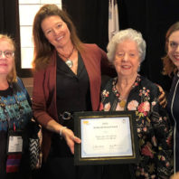 Four women in nursing hold plaque presented at conference.
