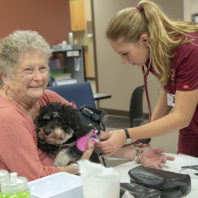 Woman holding pet dog as nursing student checks her blood pressure.