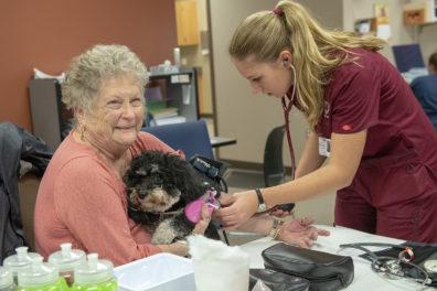 Woman holding pet dog as nursing student checks her blood pressure.
