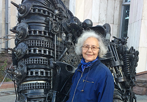 Tolmacheva stands beside a sculpture of black metal, chains and gears.