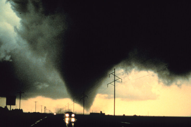 Large tornado in distance and car attempting to escape.