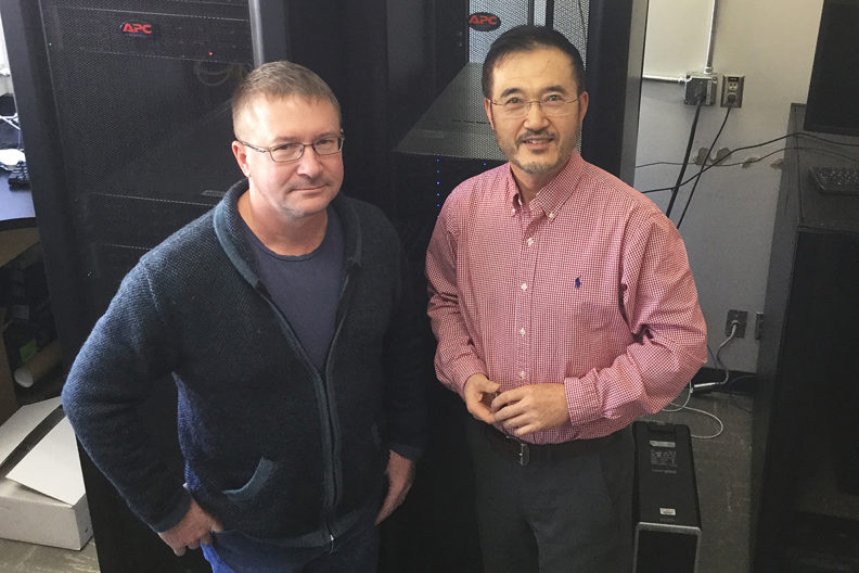 See and Zhang standing in front of large computer equipment.