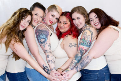Six women standing together, each with an arm joining other arms in the middle.