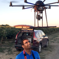 Khot manning controls with drone hovering overhead, next to vineyard.