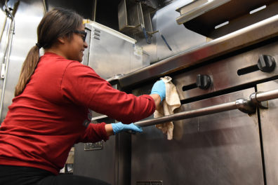 WSU student cleans the UGM kitchen stove.