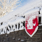 WSU sign at entrance to Pullman campus covered in snow.