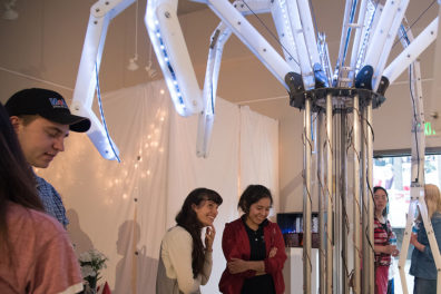 Visitors look at an unusual-shaped robotic structure with lights.