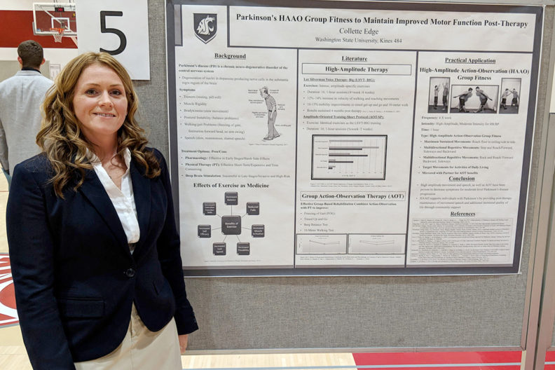 Edge standing beside research poster.