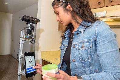 Raghunath interacts with helper robot at WSU Smart Apartment.