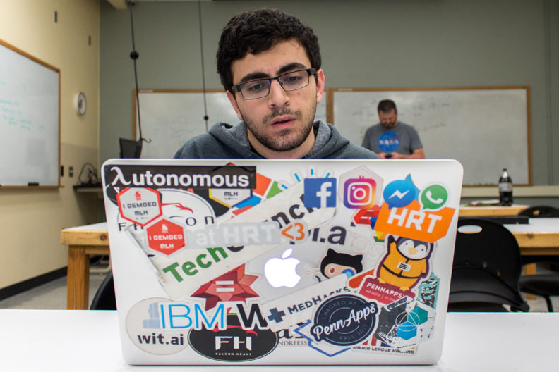 Khorram sits at laptop computer covered with stickers.