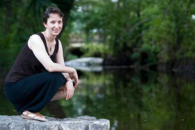Moffett kneeling on a rock next to a stream.