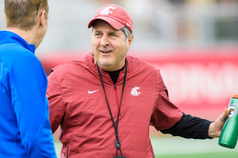 Leach smiling during conversation with someone on football field.