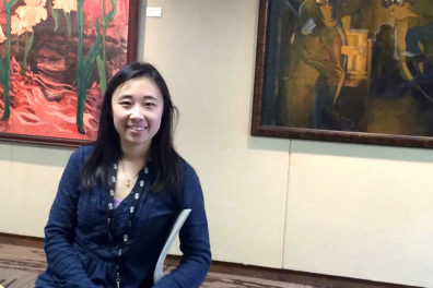 Zhang standing in front of large paintings.