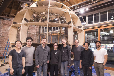 Members of the WSU Circum-ambience project team in front of a globe-shaped, wood-frame structure.