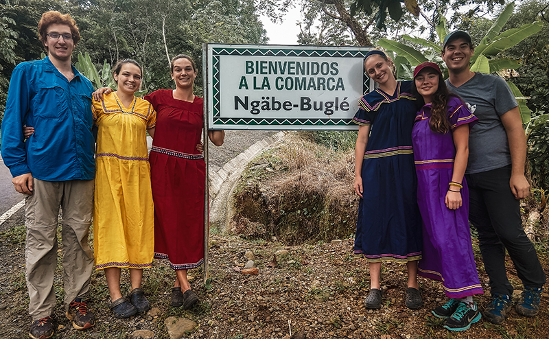 People standing beside sign reading 'Bienvenidos a la Comarca Ngabe-Bugle'.