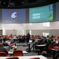 Whitman lecturing to a classroom of students in a state of the art videoconferencing facility.