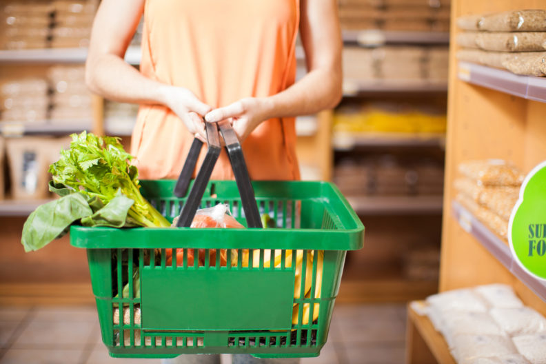Closeup of woman holding basket full of groceries.