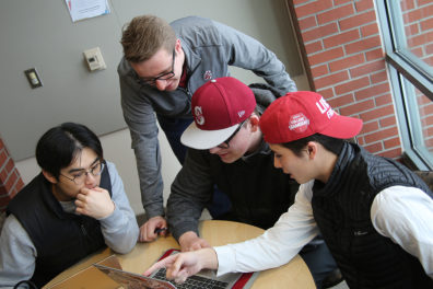 Students gathered around laptop discussing upcoming conference.