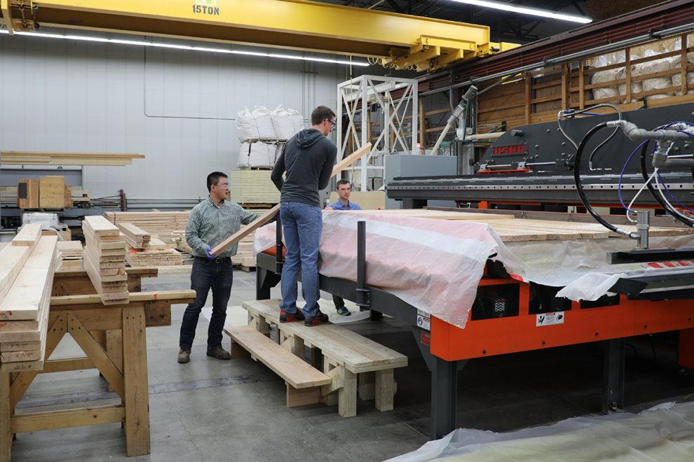 Researchers feeding lumbar materials through CLT manufacturing system.