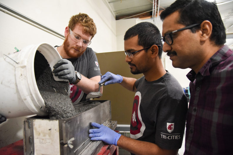 Allena and students in lab pouring grout into a rectangular.