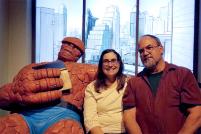 Jan and Mark O'English sit on couch with Marvel hero The Thing.
