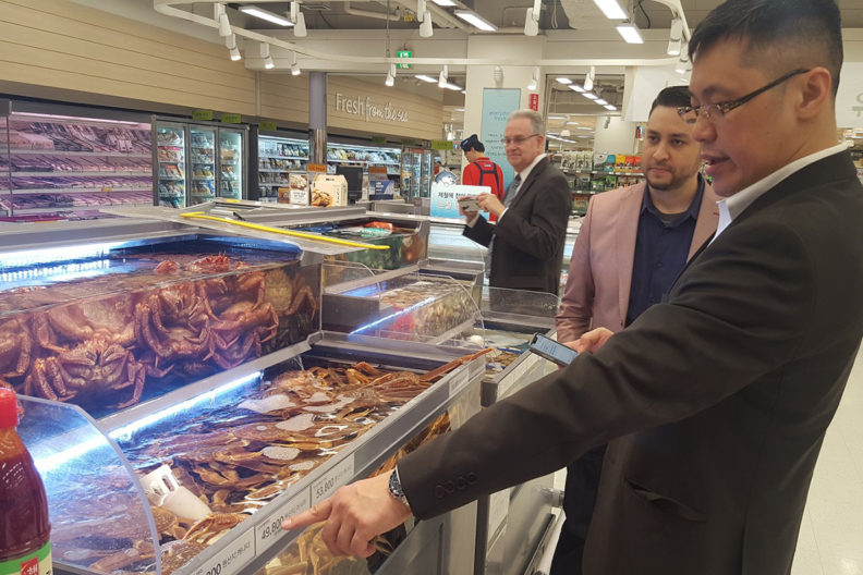 Wen, Shulman and Jenkins looking at seafood in a refrigerated display in grocery store.