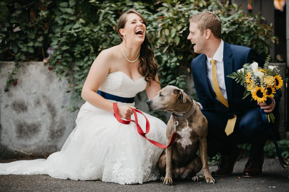 Bride and groom kneeling and laughing with dog.