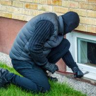 Burglar with crowbar breaking into house through basement window.