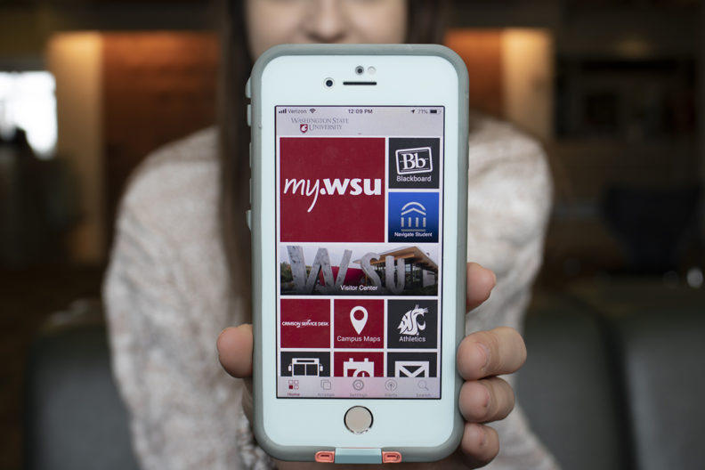Woman shows smart phone with myWSU app open.