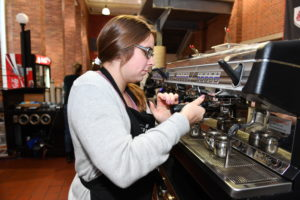 Atrium barista using the new espresso machines.