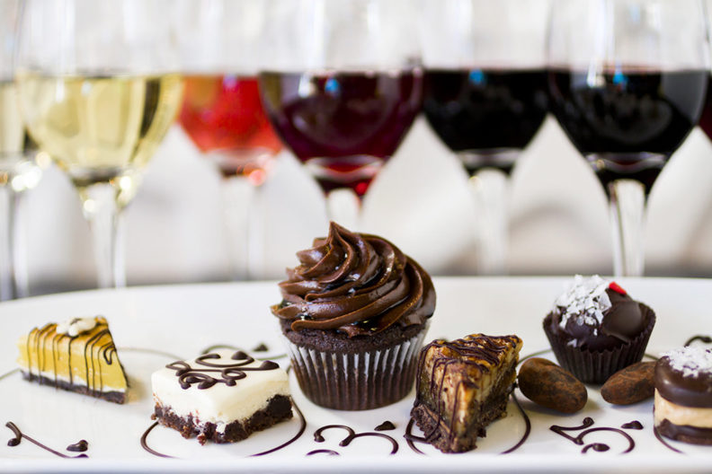 Glasses of wine and an assortment of chocolates.