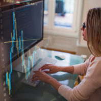 Business charts and a woman typing on a computer keyboard.