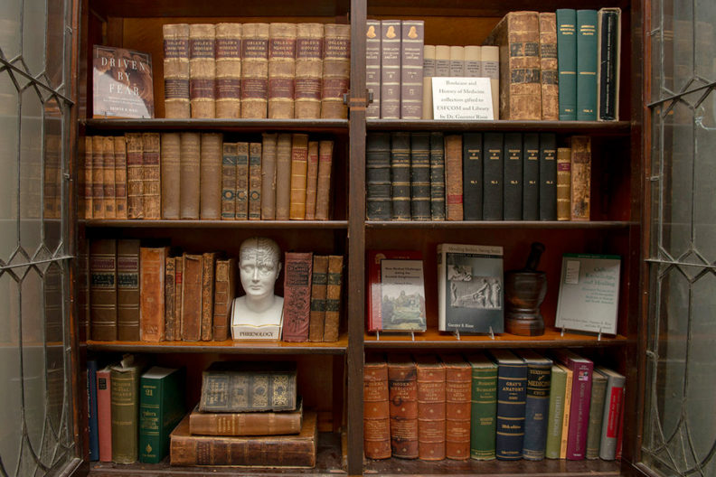 Antique bookcase filled with medical books.