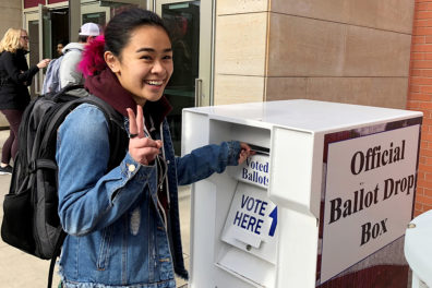 Student dropping ballot off in official ballot box.