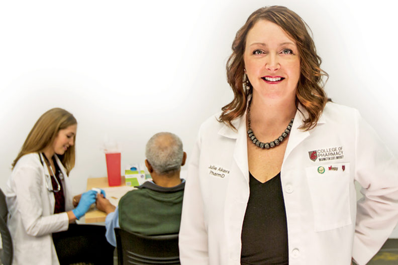 Julie Akers stands in foreground as pharmacy student assists a patient.